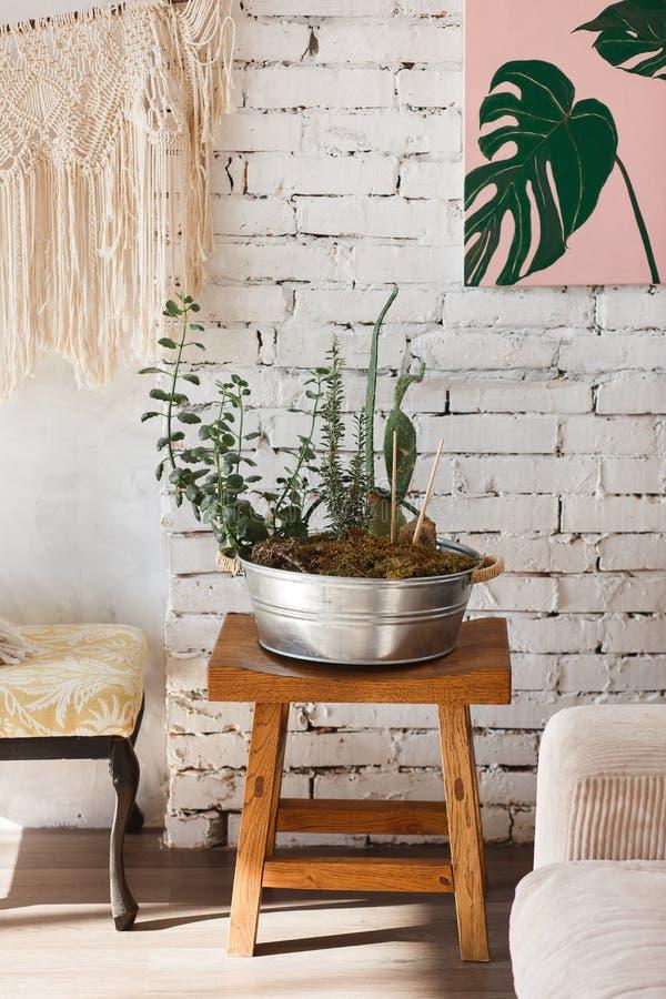 Interior moderno del desván con las flores en pote grande del metal Pared de ladrillo blanca en fondo fotos de archivo