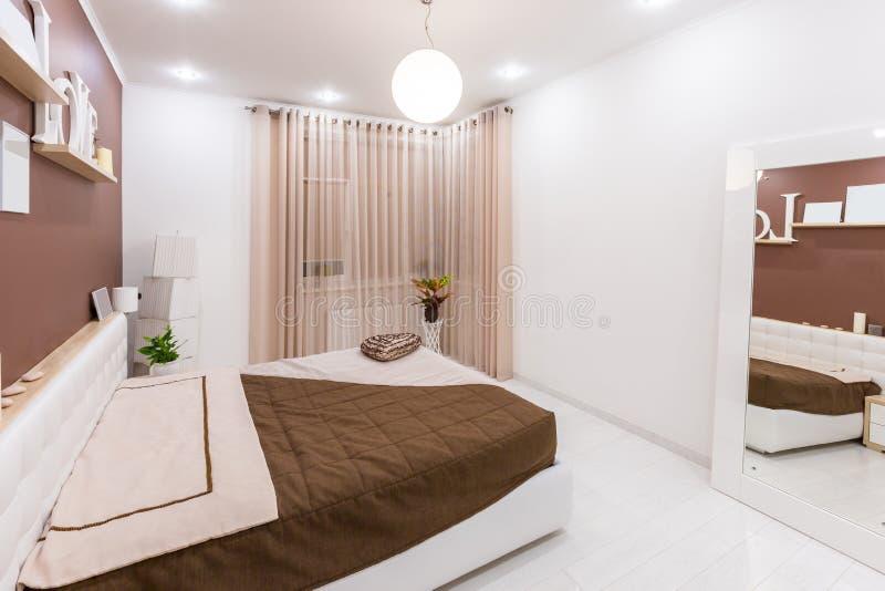 Interior moderno del dormitorio del estilo del minimalismo en tonos calientes ligeros imagenes de archivo