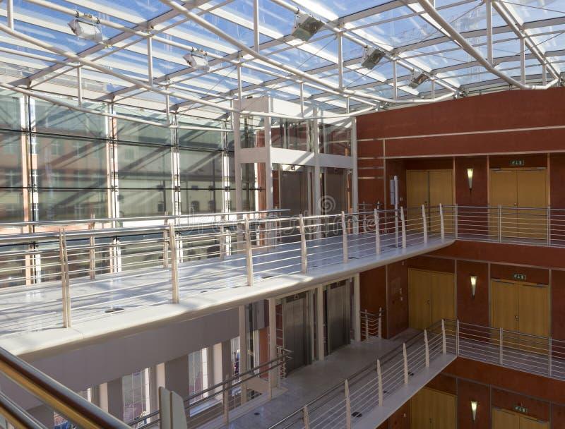 Interior moderno del edificio de oficinas con las paredes y tejado de cristal, pasillo y elevaciones, luz natural del sol fotografía de archivo libre de regalías