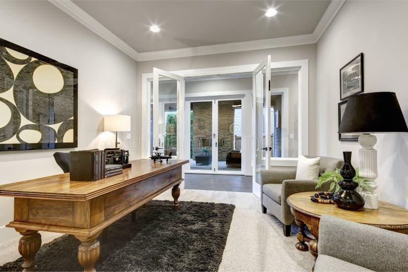 Interior moderno do escritório domiciliário com a grande tabela de madeira e a vista de imagens de stock