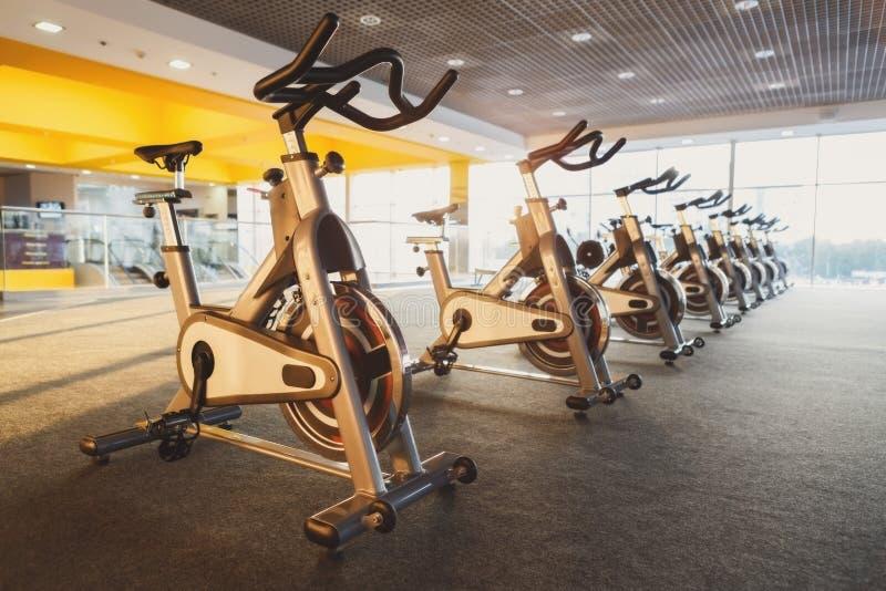 Interior moderno do gym com equipamento, bicicletas de exercício da aptidão imagens de stock