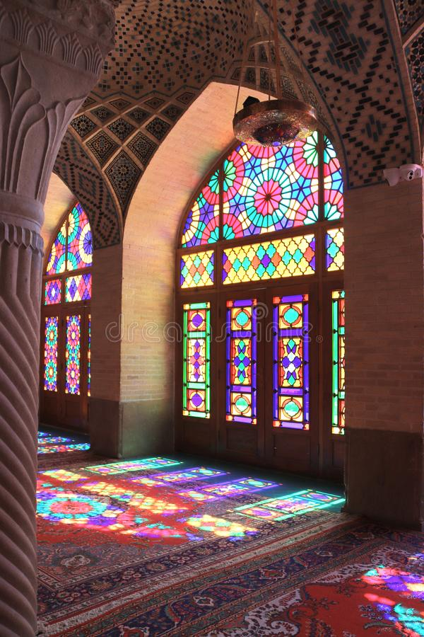 Interior of Nasir al-Mulk mosque Pink mosque, Shiraz, Iran. Beautiful patterns of sunlight on carpets through multi-colored stained-glass windows. Interior of royalty free stock photos