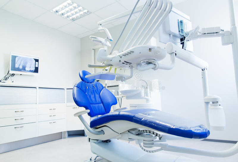 Interior of new modern dental clinic office. Dentistry, medicine, medical equipment and stomatology concept - interior of new modern dental clinic office with royalty free stock image
