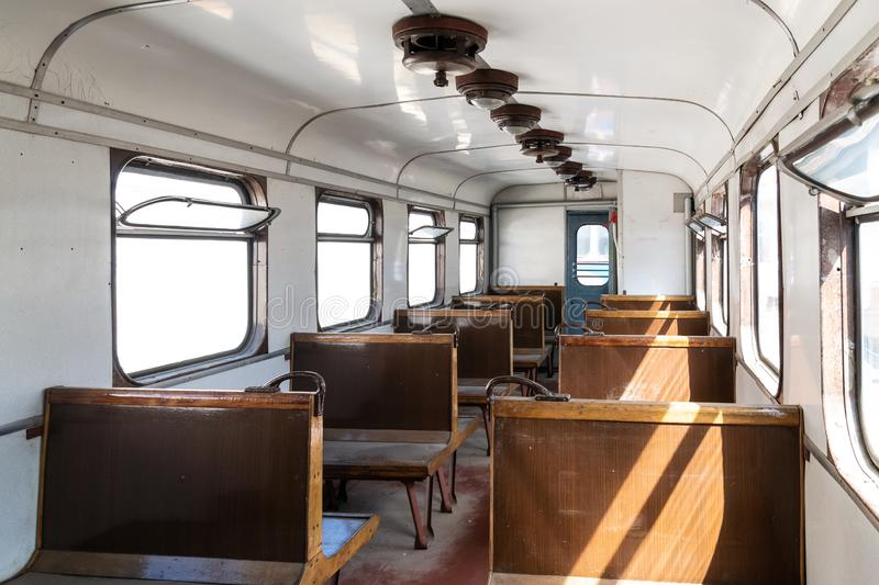 Interior of an old passenger car on a railroad. Historic vintage train Slightly left angle. Rows of seats and old style furnishing. S royalty free stock photo