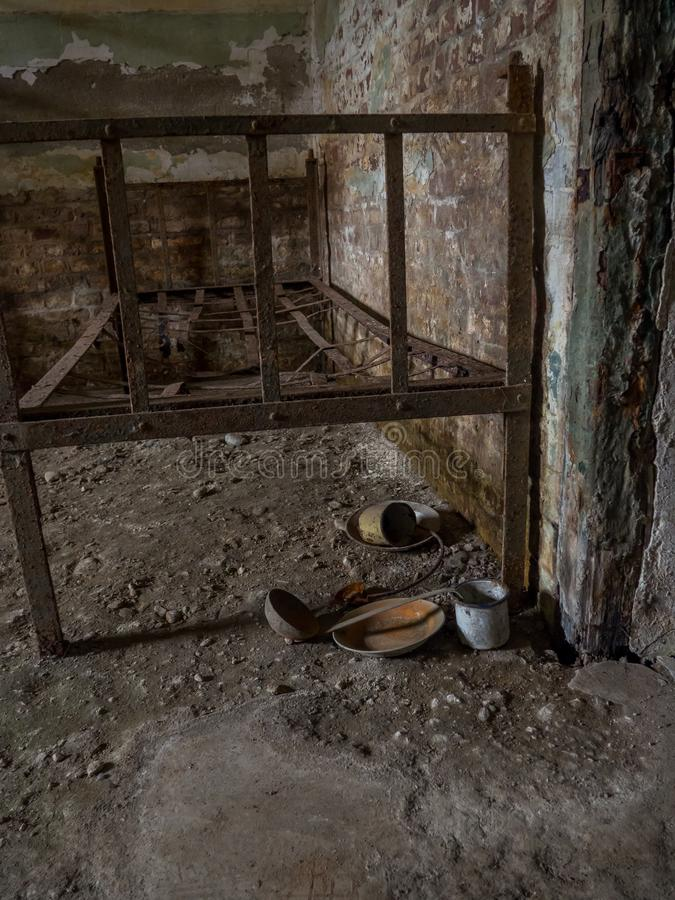 Interior of old prison cell with rusted bed and old rusted kitchenware royalty free stock image