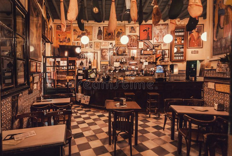 Interior of old restaurant with vintage style decoration waiting for customers and hungry tourists. SEVILLE, SPAIN - NOV 15: Interior of old restaurant with stock photos