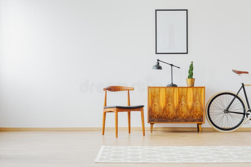 Interior with old restored furniture. Old restored furniture in contemporary bright interior with white wall and vintage accessories, chair, lamp, wooden stock photography
