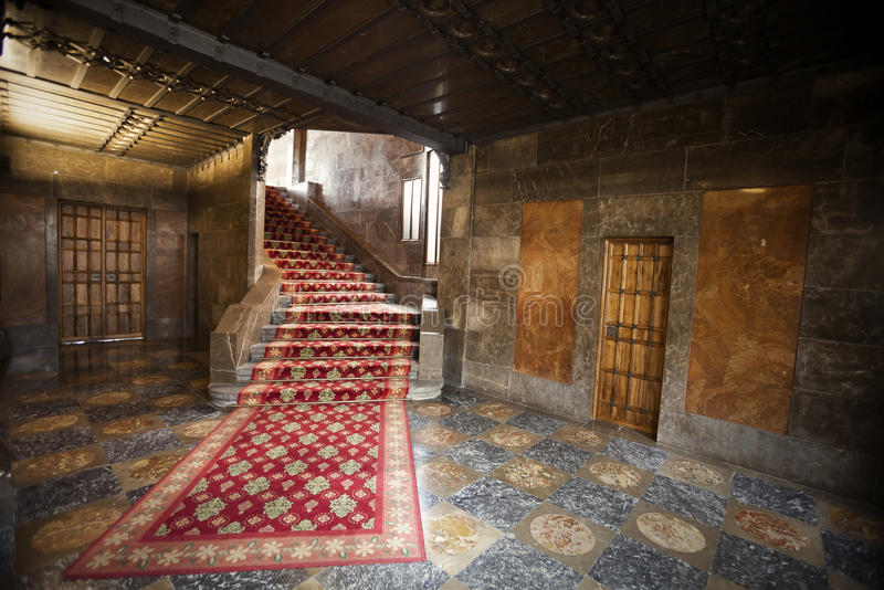 Interior of an old Spanish house with red carpet, stairs and doors royalty free stock image