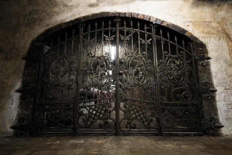 Interior of an old wine cellar, a forged iron gate stock photo