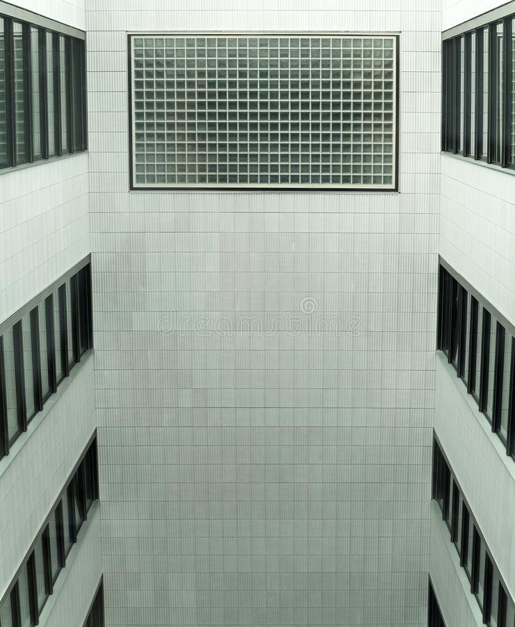 Interior open courtyard in a modern multi-storey building. Enclosed interior open courtyard in a modern multi-storey building with black framed windows stock photo