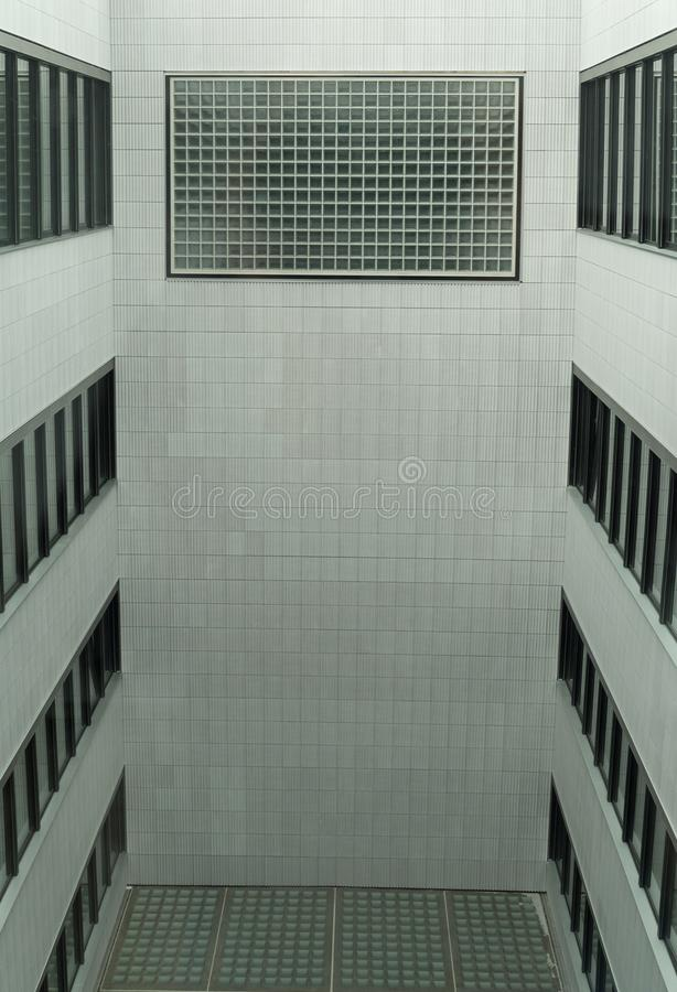 Interior open courtyard in a modern multi-storey building. Enclosed interior open courtyard in a modern multi-storey building with black framed windows stock images