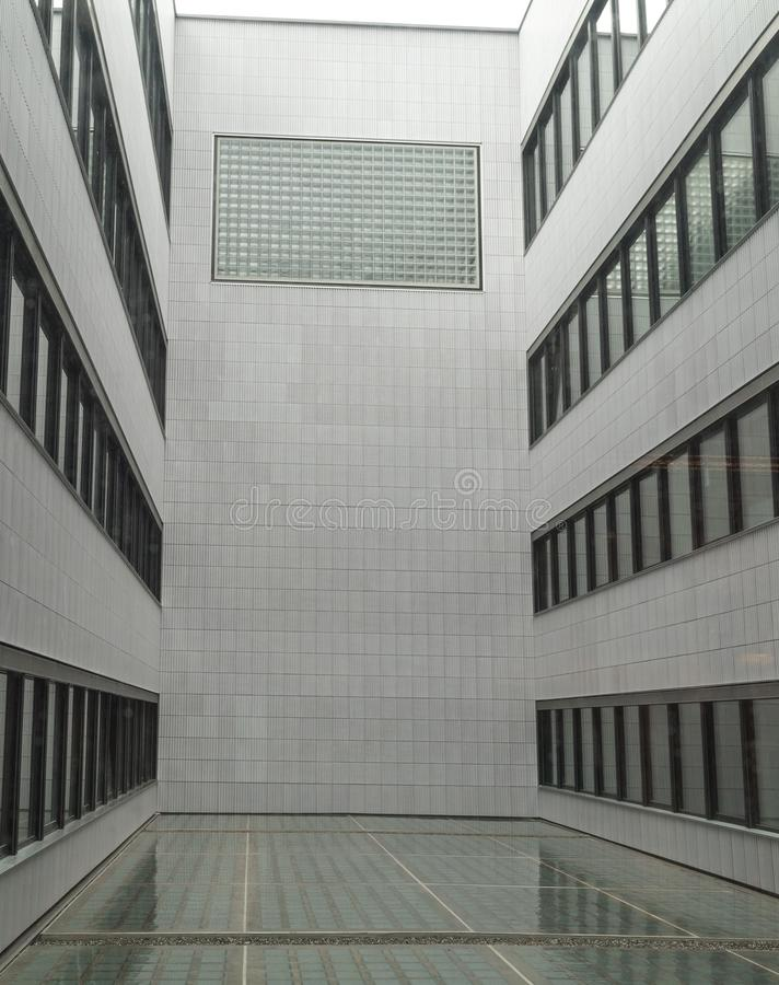 Interior open courtyard in a modern multi-storey building. Enclosed interior open courtyard in a modern multi-storey building with black framed windows royalty free stock photography