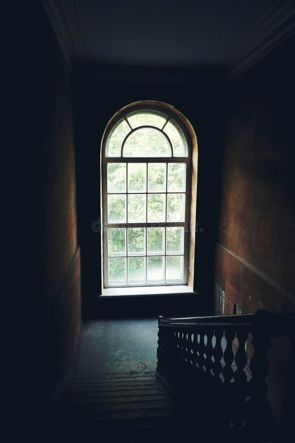 Interior oscuro de la escalera del vintage en el edificio viejo, escalera con la verja de madera, ventana grande con la luz del d fotos de archivo libres de regalías