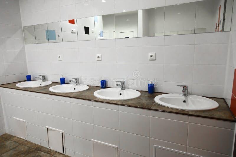 Interior público do banheiro dos homens do toalete vazio com os dissipadores da mão da lavagem Espelho com a bacia de mão no toal fotografia de stock