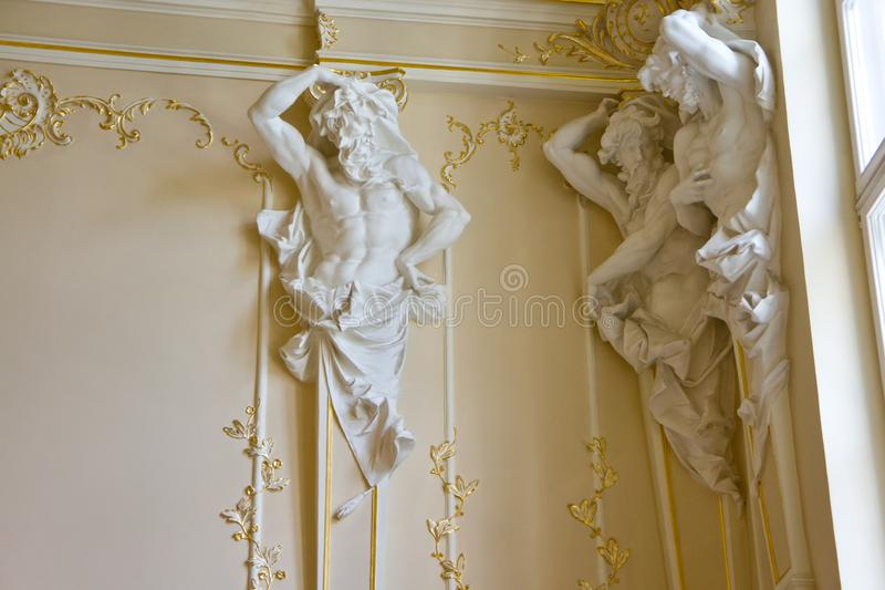 Interior of the palace with statues supporting the ceiling and beautiful stucco royalty free stock images