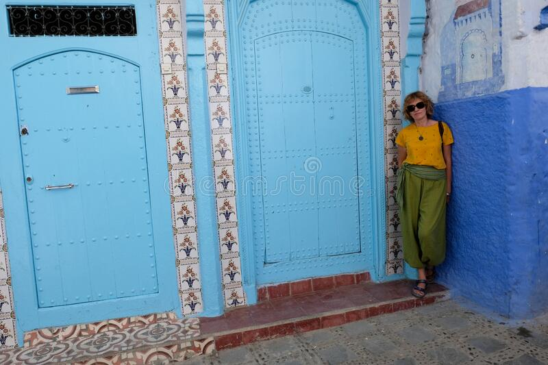 Interior portrait of a middle-aged woman in blue city of Chefchaouen,Morocco stock photo