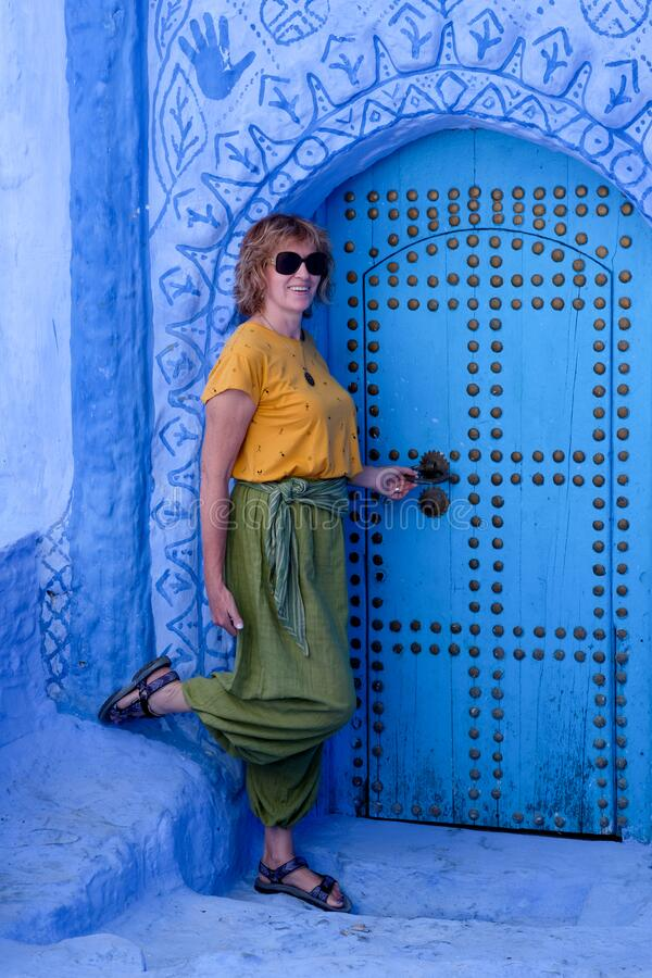 Interior portrait of a middle-aged woman in blue city of  Chefchaouen,Morocco stock photography