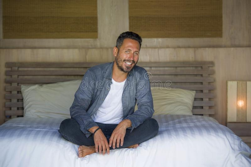 Interior portrait of 30s happy and handsome man at home in casual shirt and jeans sitting on bed relaxed at home smiling confident royalty free stock photo