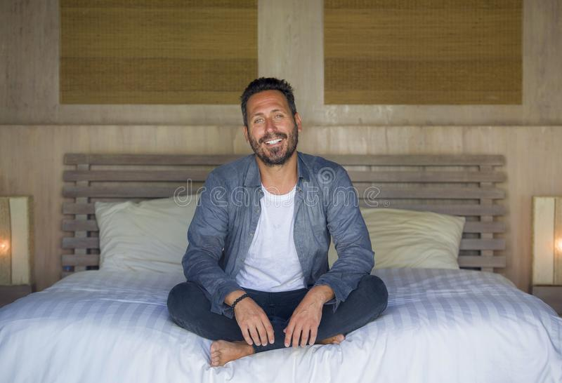 Interior portrait of 30s happy and handsome man at home in casual shirt and jeans sitting on bed relaxed at home smiling confident stock image