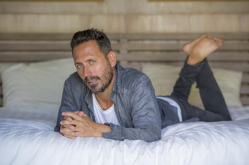 Interior portrait of 30s to 40s happy and handsome man at home in casual shirt and jeans lying on bed relaxed at home smiling royalty free stock image