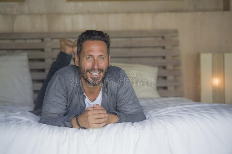 Interior portrait of 30s to 40s happy and handsome man at home in casual shirt and jeans lying on bed relaxed at home smiling royalty free stock photography