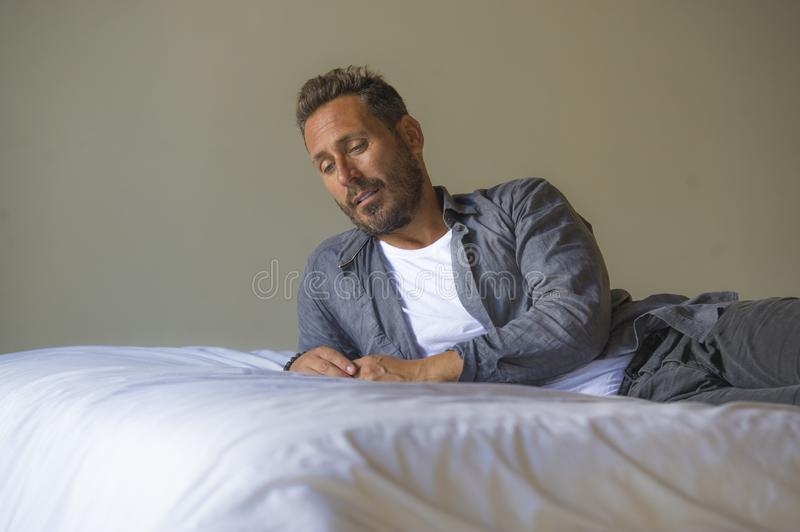 Interior portrait of 30s to 40s happy and handsome man at home in casual shirt and jeans lying on bed relaxed at home thoughtful royalty free stock photos