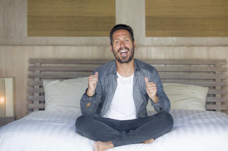 Interior portrait of 30s to 40s happy and handsome man at home in casual shirt and jeans sitting on bed relaxed at home smiling stock image