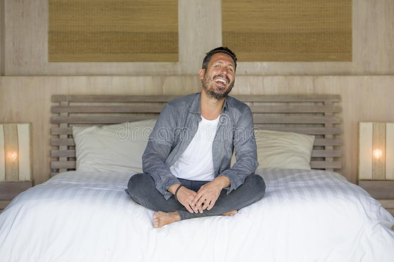 Interior portrait of 30s to 40s happy and handsome man at home in casual shirt and jeans sitting on bed relaxed at home smiling royalty free stock photos