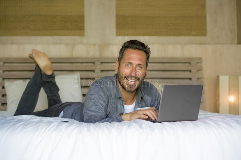 Interior portrait of young attractive and happy man at home working relaxed on bed with laptop computer smiling cheerful in stock photo