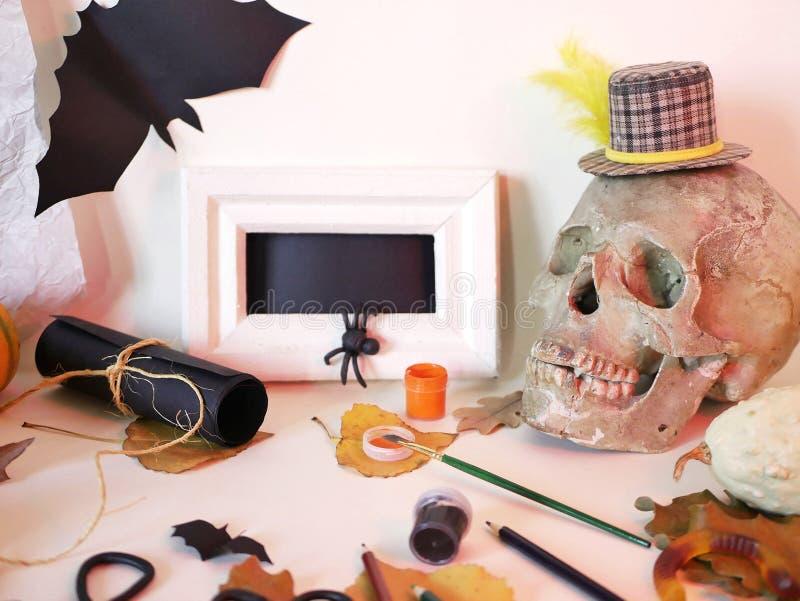 Interior preparation for Halloween. Decorative composition of a skull, pumpkins, mystical decor, art materials, leaves, interior preparation for Halloween, top stock photo