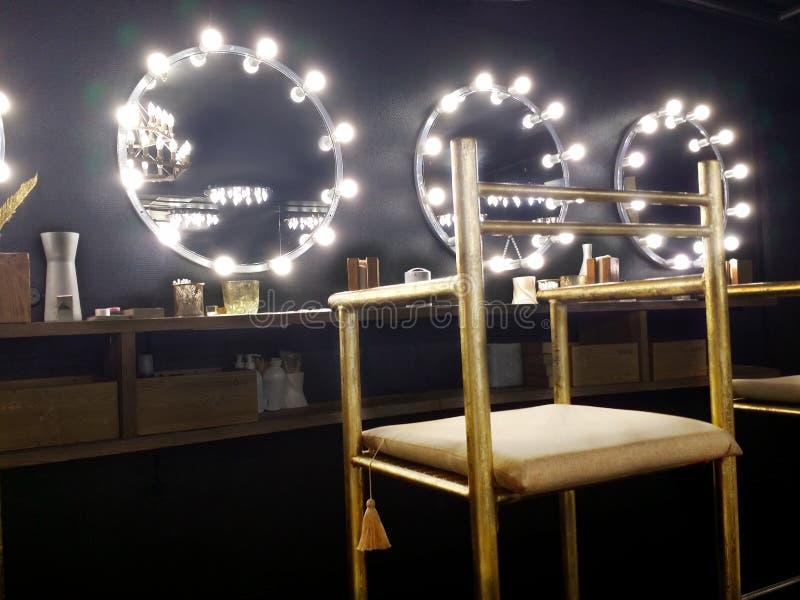 Interior preto atmosférico no salão de beleza Cadeira dourada, gasto alta no primeiro plano foto de stock royalty free