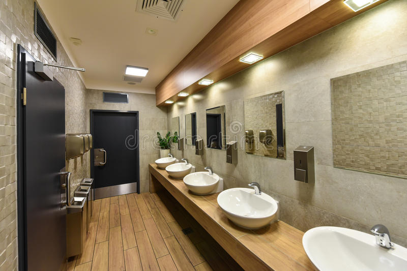 Interior of a public restroom. A row of white sinks in a public restroom royalty free stock images