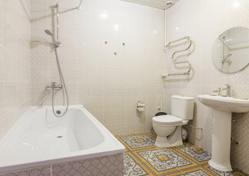 Interior razoável do hotel, banheiro combinado clássico branco com o banho e uma bacia de toalete em uma sala imagens de stock