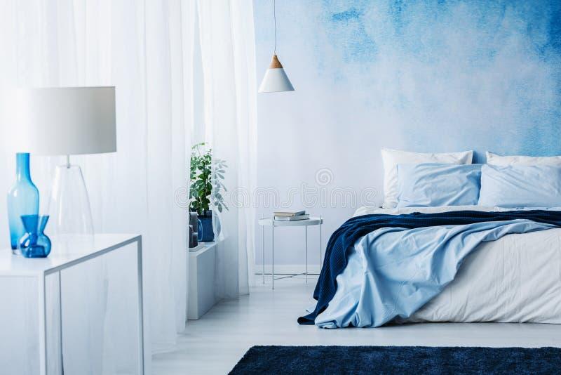 Interior relajante del dormitorio con las decoraciones blancas y azules, doubl fotografía de archivo