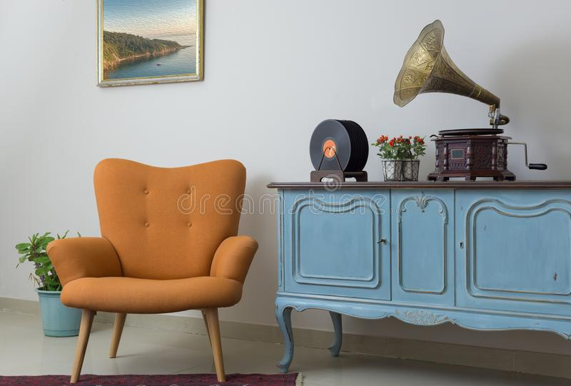Retro orange armchair, vintage wooden light blue sideboard, old phonograph gramophone and vinyl records stock photography