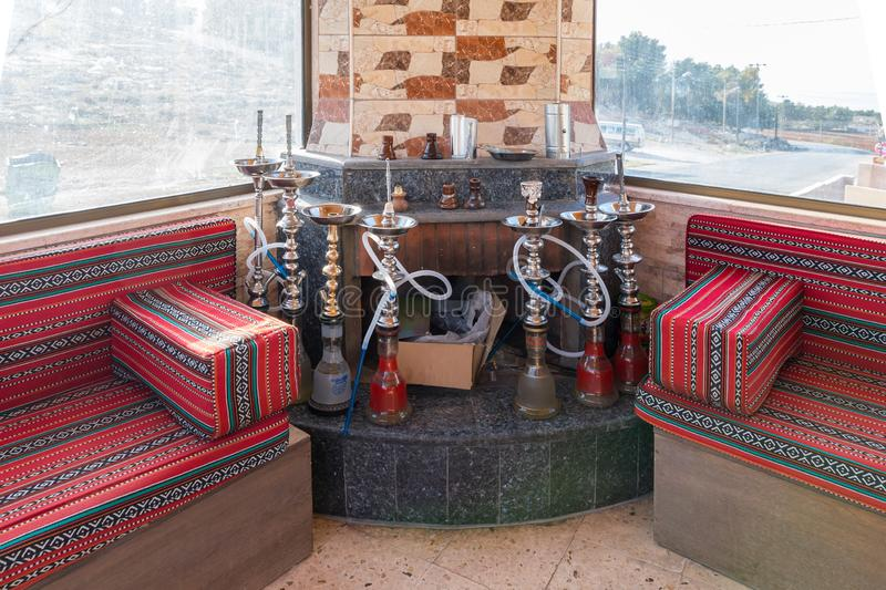 The interior of the roadside restaurant near the city Madaba in Jordan. Nargilas stand in the corner between sofas waiting for vis stock photos