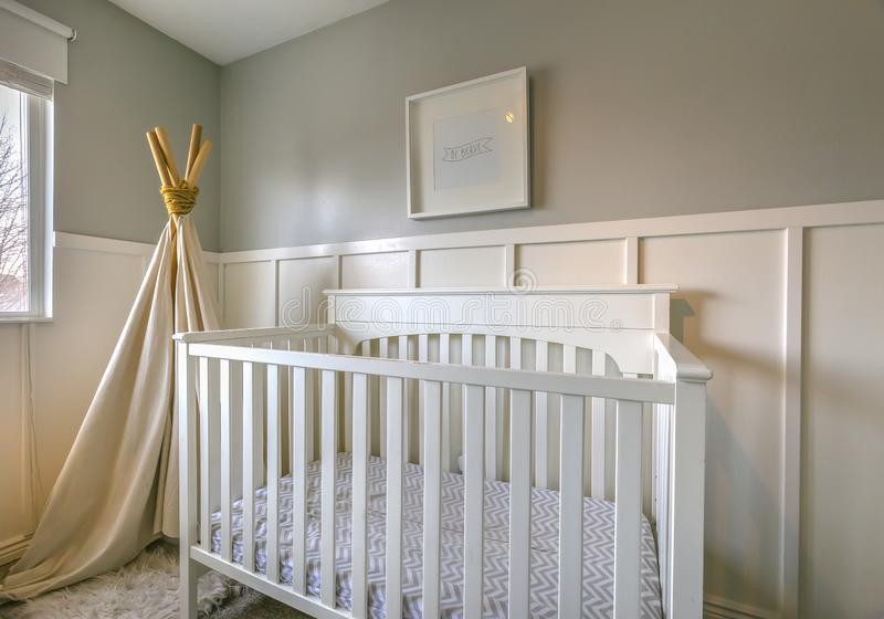 Interior of a room for children with white wooden crib and play teepee. Sunlight streams inside the room with panellings on the wall through the glass window stock photography