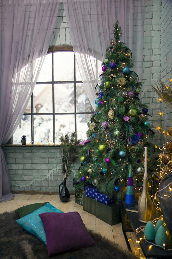 Interior room decorated in Christmas style. Xmas tree decorated by lights, presents, peacock feathers, gifts, toys, candles. royalty free stock photography