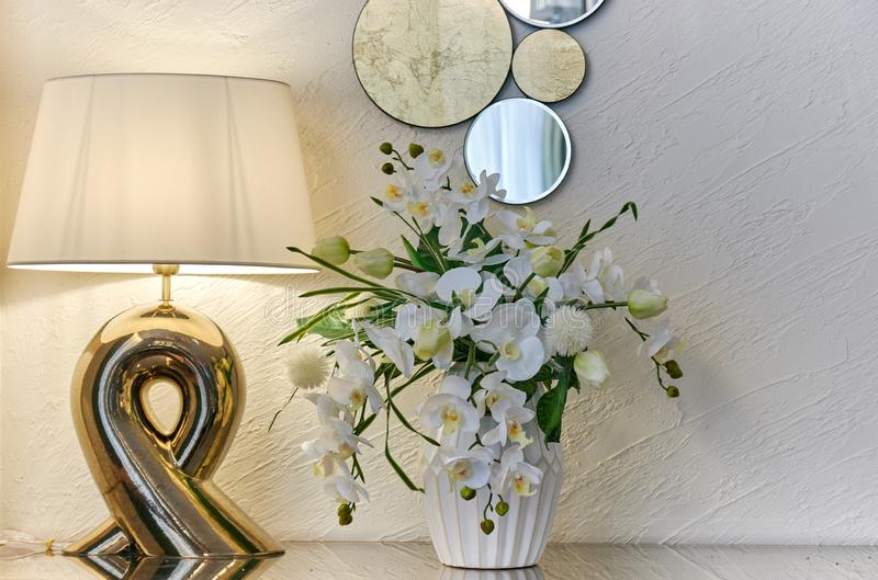Interior room lamp vase with flowers and a decorative mirror on a light wall stock photo