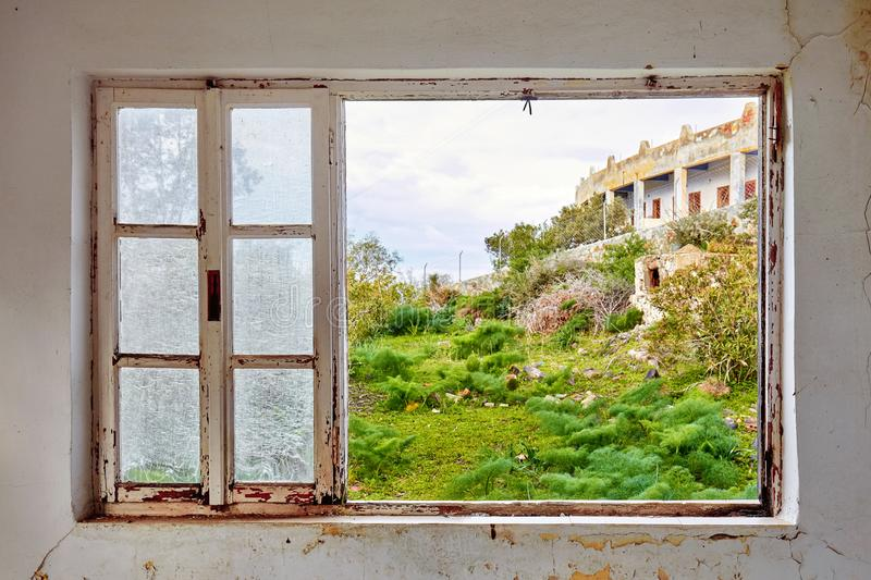 Interior of a ruined house with a broken window frame viewing a green meadow field landscape royalty free stock image