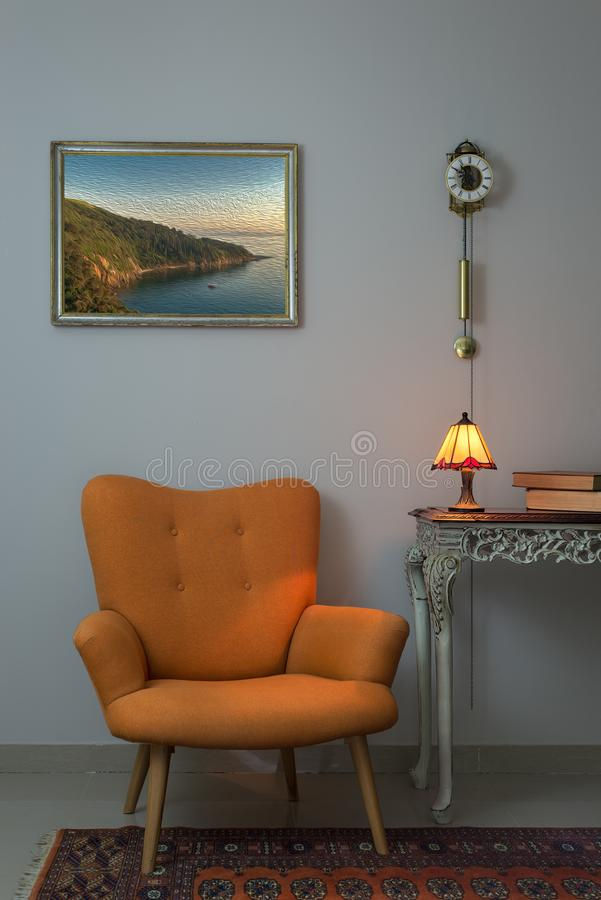 Interior shot of retro orange armchair, vintage wooden beige table, illuminated antique table lamp, old books, and pendulum clock royalty free stock photos