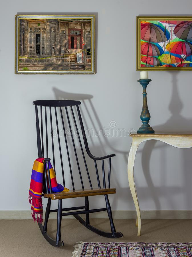 Interior shot of vintage rocking chair, old style table, candlestick on background of off white wall with two hanged paintings stock photography