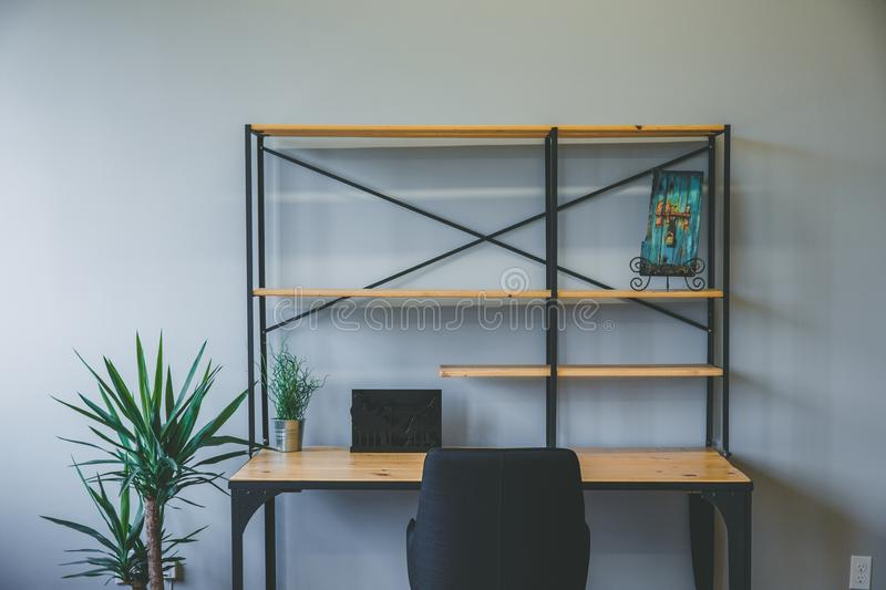 Interior shot of a wooden brown desk with empty shelves and a chair with a plant on the side stock photo
