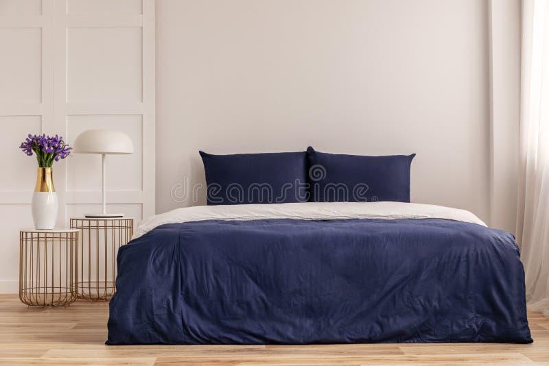 Interior simple del azul marino y blanco del dormitorio con la cama acogedora con las almohadas y el edred?n foto de archivo