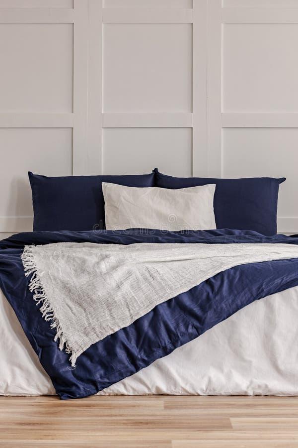 Interior simple del azul marino y blanco del dormitorio con la cama acogedora con las almohadas y el edred?n imagen de archivo