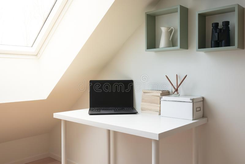 Interior simple del espacio de trabajo debajo de la ventana del tragaluz en ático/desván imagen de archivo