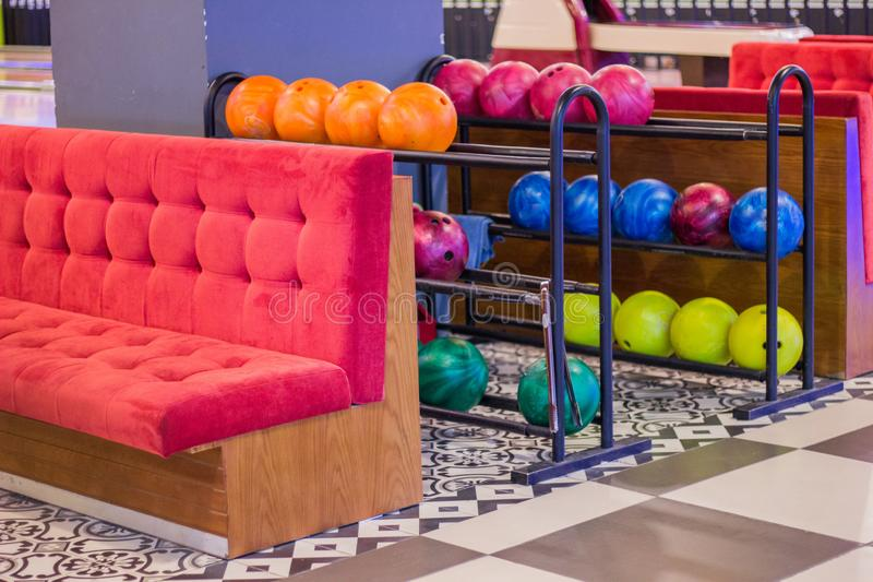 Interior of sitting area in bowling club. Comfortable red soft sofa and shelves with colorful bowling balls. royalty free stock photos