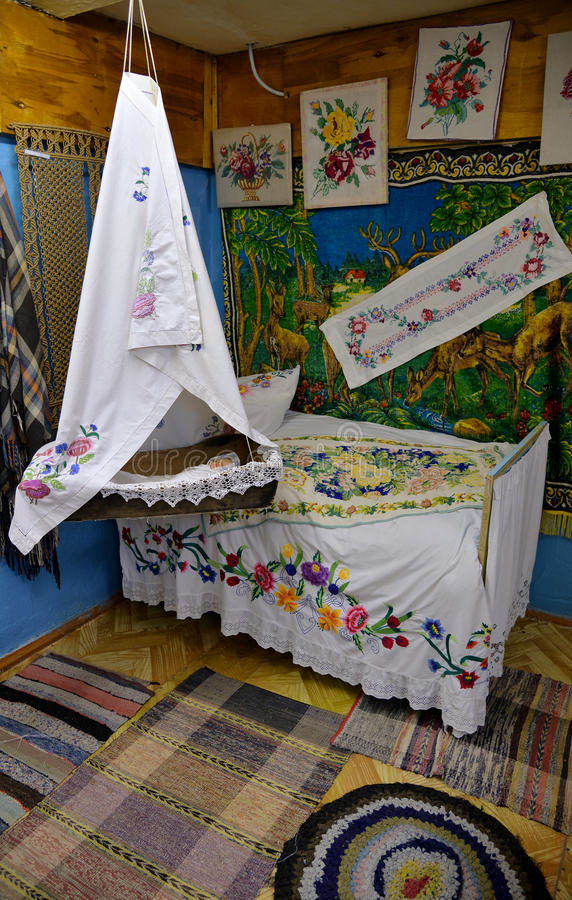 Interior of sleeping room with bed and old cradle decorated with embroideries in Russian style stock photos