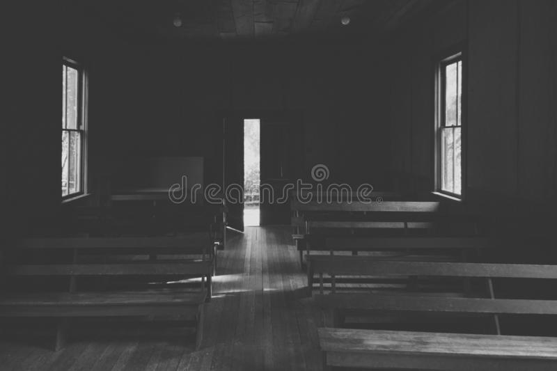 An interior of a small church in the countryside with wooden benches and an opened door stock photos