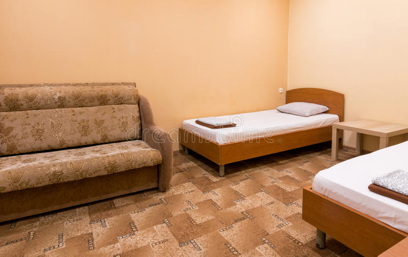 Interior of a small room with a sofa and two beds stock image